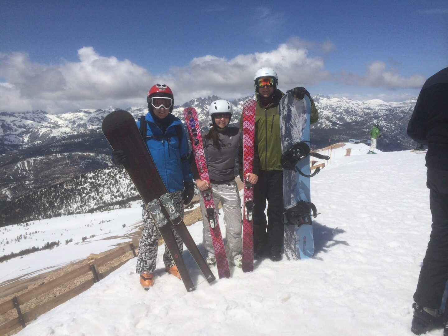 three people holding monoski, snow skis, and snowboard
